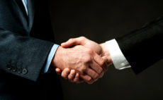 Business partners shaking hands, closeup shot